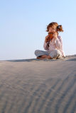 Little girl play pan pipe in desert Stock Photography