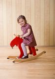 Happy little girl play with toy wooden deer Stock Photography