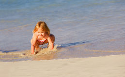 Happy little girl play with water at beach Royalty Free Stock Photo