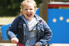 Happy little girl at playground royalty free stock image