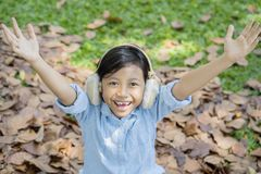 Happy little girl playing with autumn foliage. Picture of cute little girl looks happy while playing in the park with autumn foliage Stock Photography