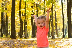 Happy little girl playing in autumn park royalty free stock image