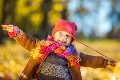 Happy little girl playing in the autumn park Royalty Free Stock Photo