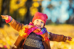 Happy little girl playing in the autumn park Stock Photos