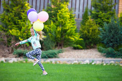 Happy little girl playing with balloons outdoors Stock Image