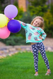 Happy little girl playing with balloons outdoors Royalty Free Stock Photos