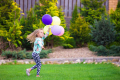 Happy little girl playing with balloons outdoors Royalty Free Stock Image