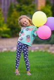 Happy little girl playing with balloons outdoors Stock Photography