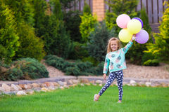 Happy little girl playing with balloons outdoors Royalty Free Stock Images