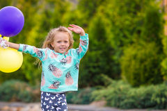 Happy little girl playing with balloons outdoors Royalty Free Stock Photo