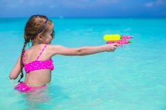 Happy little girl playing at beach during Stock Photography