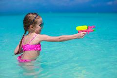 Happy little girl playing at beach during Stock Photos