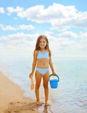 Happy little girl playing on the beach near sea Royalty Free Stock Photos