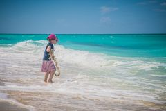 Kid at the ocean. Happy little girl playing on the beach. Holiday, outdoors. stock image