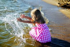 Happy little girl playing on the beach. At sunny summer day Stock Photography