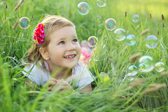 Happy little girl playing with bubbles. Sweet, happy, smiling three year old girl laying on a grass in a park playing with bubbles Stock Photography
