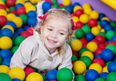 Happy little girl playing on colorful balls Royalty Free Stock Photos