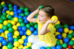 Happy little girl playing at colorful plastic balls playground. Happy little girl playing with colorful plastic balls atplayground Stock Photo