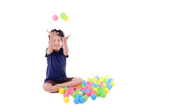 Happy little girl playing with colourful balls Stock Images