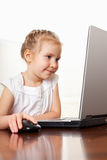 Happy little girl playing computer Royalty Free Stock Photography