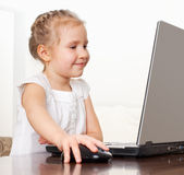 Happy little girl playing computer Stock Images