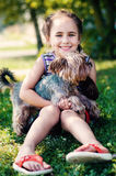 Happy little girl playing with dog. On the grass Royalty Free Stock Images