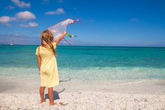 Happy little girl playing with flying kite during Royalty Free Stock Images