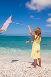 Happy little girl playing with flying kite during Royalty Free Stock Photos