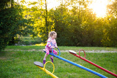 Happy little girl playing, going up ad down on a seesaw Stock Photo