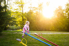Happy little girl playing, going up ad down on a seesaw Royalty Free Stock Photo