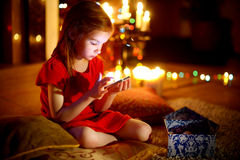 Happy little girl playing with her smart phone on Christmas eve Stock Photo