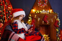 Happy little girl playing with her smart phone by a fireplace in a cozy dark living room on Christmas eve stock image