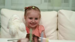 Happy little girl playing her toy at birthday table stock video footage