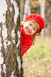 Happy little girl playing hide and seek outdoors. Cute happy little girl playing hide and seek outdoors Royalty Free Stock Photography