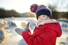 Happy little girl playing with ice blocks by frozen river during an ice break. Child having fun in winter. stock photography
