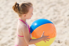 Happy little girl playing inflatable ball on beach Stock Image