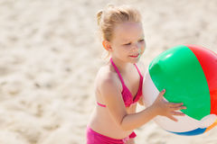 Happy little girl playing inflatable ball on beach Stock Images