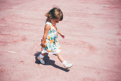 Happy little girl playing outdoors. Happy little girl playing outdoors in the day. Lifestyle welfare Royalty Free Stock Image