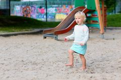 Happy little girl playing outdoors Stock Image