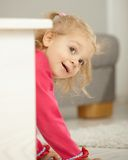 Happy little girl playing peek-a-boo Stock Images
