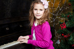Happy little girl playing the piano. Sitting near the a Christmas tree Royalty Free Stock Photo