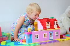 Happy little girl playing with plastic blocks Royalty Free Stock Photo