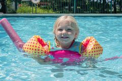 Happy little girl playing at the pool. On a summer day stock photography