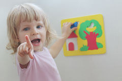 Happy little girl playing with puzzles Stock Photography