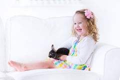 Happy little girl playing with a rabbit Royalty Free Stock Images