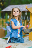 Happy little girl playing in sandbox at playground Stock Image