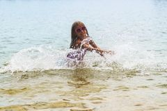 Happy little girl playing in shallow water waves.little girl playing in the sea waves,Girl Having Fun In Sea Waves. Happy girl in stock photos