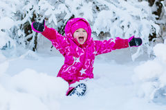 Happy little girl playing in the snow Stock Images
