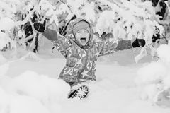 Happy little girl playing in the snow Stock Photos
