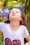 Happy little girl playing with soap bubbles on a summer nature, wearing a blue ears tiger accessories over her head in a Stock Photo